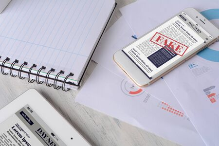 Close up of spiral notepad, tablet, financial papers and smartphone with digital fake News on screen. Propaganda and disinformation online. Media and digital concept. All screen graphics are made up b