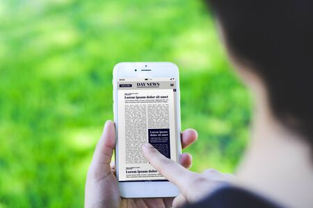 Primo piano della giovane donna che legge le ultime notizie sullo smartphone. Concetto di giornale digitale. Tutta la grafica dello schermo è composta da noi Archivio Fotografico