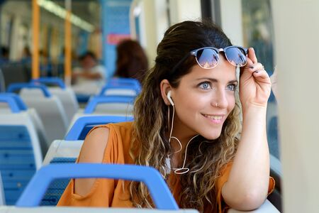 Young woman looking through the window in a train. Business people. Imagens