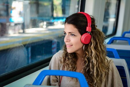 Young woman travelling by train with red headphones. Zdjęcie Seryjne