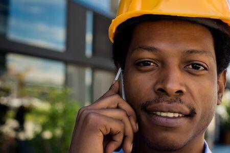 Professional man in helmet talking on the phone at street.