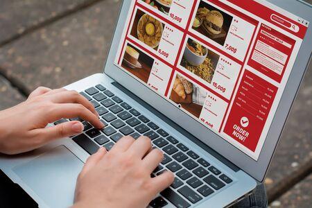 Mujer de cerca con ordenador portátil pedir comida para llevar en línea. Concepto de entrega. Todos los gráficos de pantalla están hechos por nosotros. Foto de archivo