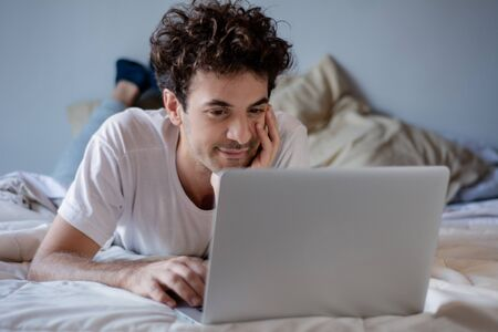 Happy young man using laptop on his bed. Indoors