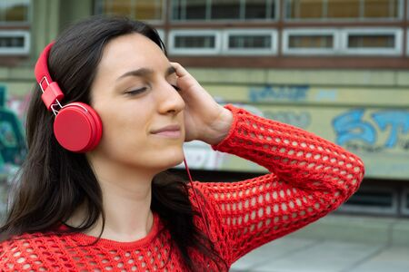Portrait of young woman listening to music with red headphones. Outdoors.