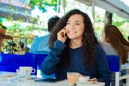 Portrait of beautiful young latin woman talking on mobile phone at coffee shop.
