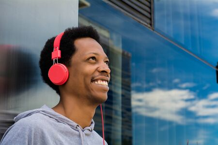 Young latin man listening music with headphones in the city. Enjoying concept.