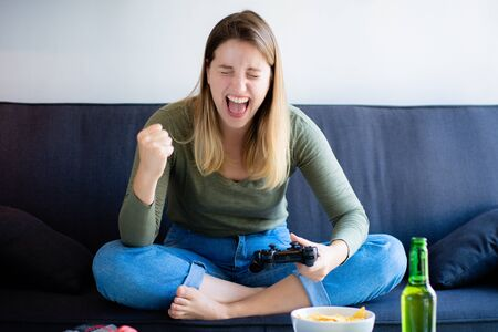 Portrait of young woman playing video games on sofa at home. Video game concept.