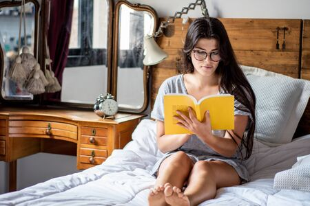 Young woman reading book on bed. concepts of home and comfort.