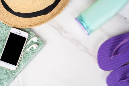 Close-up of a hat, smartphone, flip flops, sunscreen and a towel. Travel concept. Фото со стока - 130136749