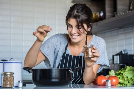 Young Woman Cooking in the kitchen at home. Healthy Food. Фото со стока