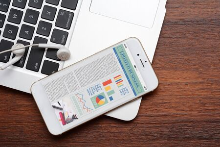 Close up view of keyboard, earphones  and smartphone with statistics, charts and graphic information about company growth. Business concept. All screen graphics are made up by us