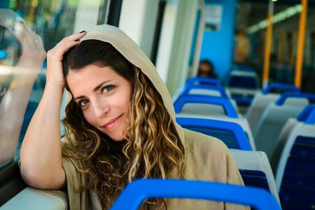 Young beautiful woman tourist traveling by the train sitting near the window. Enjoying travel concept.