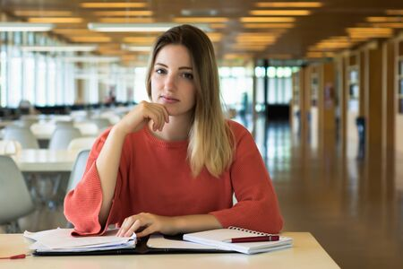 Portrait of Young female student working in the university library. Stock fotó