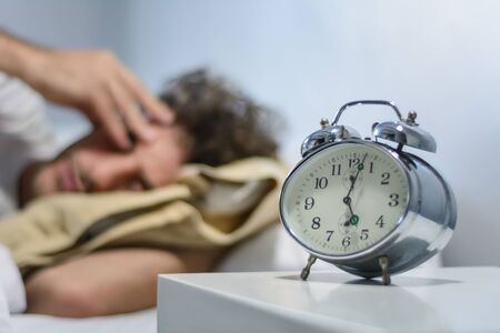 Young latin man hates waking up early in the morning with alarm clock. Indoors. 版權商用圖片 - 130136766