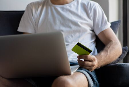 Young man with laptop computer and credit card at home. Shopping and lifestyle concept.