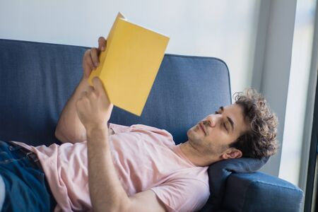 Attractive young man relaxed and reading a book on sofa at home. Indoors. Stock fotó