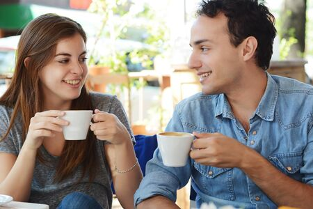 Young attractive couple enjoying a coffee at the coffee shop. Outdoors.