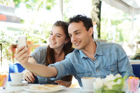 Young beautiful couple taking a selfie with smartphone in coffee shop.
