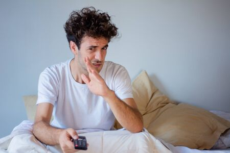 Portrait of young man watching tv and relaxed on bed. Indoors. Stock fotó