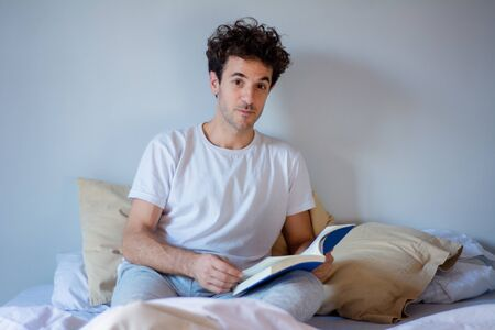 Young latin man reading a book while laying in bed at home.