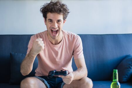 Portrait of young man playing video games in his living room. Technology and games concept.