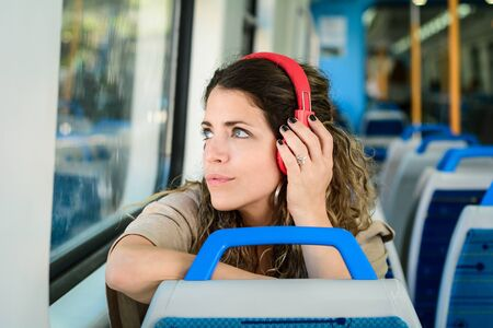 Young woman travelling by train with red headphones. Stock fotó