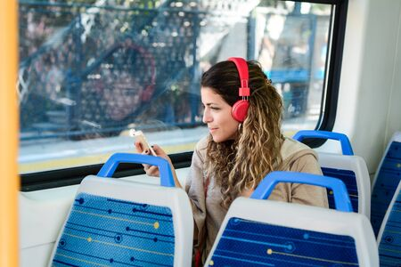 Young urban woman traveling by the train using smartphone. Woman sitting in transport enjoying travel