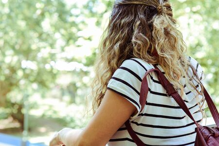 Young tourist woman from behind looking at park. Summer holidays.