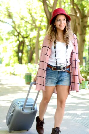 Tourist young woman carrying a suitcase on street. Enjoying, lifestyle concept.