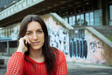 Portrait of young latin woman talking on her mobile phone. Outdoors.