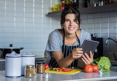 Young Woman cooking and following recipe on Digital tablet in the kitchen at home. Healthy Food.
