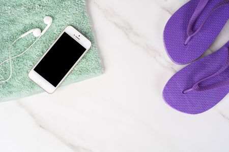Close-up of a smartphone, flip flops and a towel. Travel concept. Stock Photo