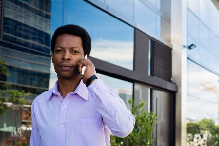 Portrait of young latin businessman talking on mobile phone in the city. Stock Photo