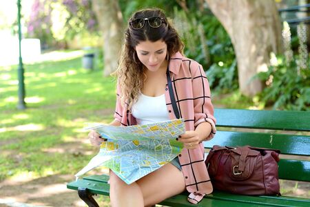 Young female traveler with map outdoors. Holidays and tourism concept Imagens