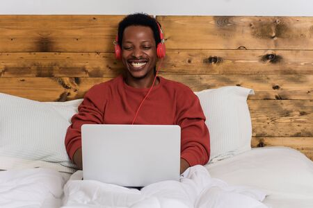 Happy young man listening music with headphones and using laptop on his bed. Indoors