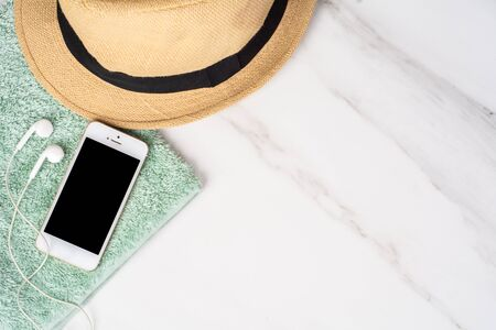 Close-up of a smartphone, hat, sunscreen and a towel. Travel concept.
