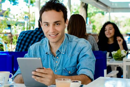 Young latin man with earphones using digital tablet in coffee shop. Stock fotó