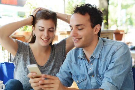 Hermosa joven pareja con smartphone en cafetería. Foto de archivo