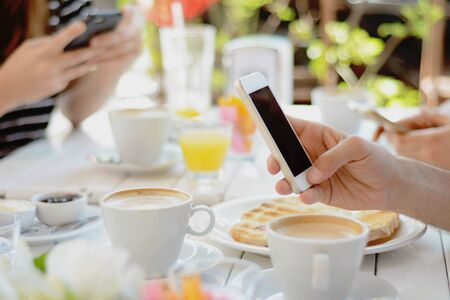Group of friends using smartphone at coffee shop. Communication concept. Stock fotó