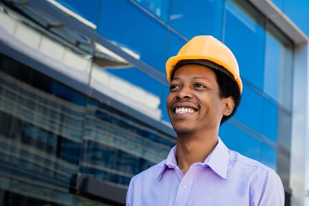 Portrait of Afro american engineer developer in hard hat outdoors. Фото со стока