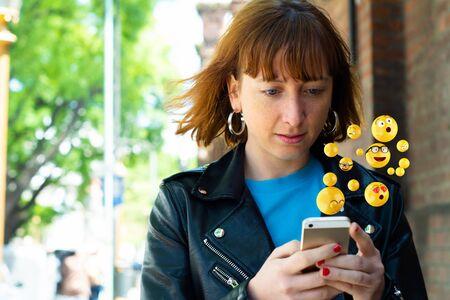 Close-up of woman using smartphone sending emojis. Social concept. Banco de Imagens