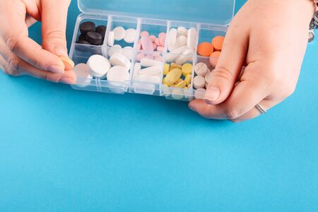 Close up of hand showing medicine box with pills on Blue background Reklamní fotografie