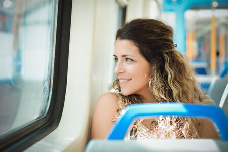 Young urban woman looking through the window in a train. Modern people lifestyle.