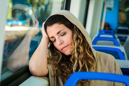 Young urban woman sleeping in a train travel beside the window. Modern people city lifestyle. 스톡 콘텐츠