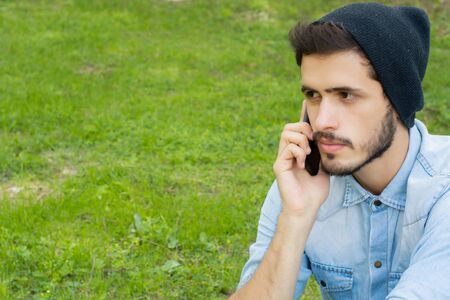 Portrait of young handsome man talking on the phone in a park. Outdoors.
