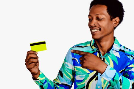 Portrait of afro american man holding a credit card on isolated background.