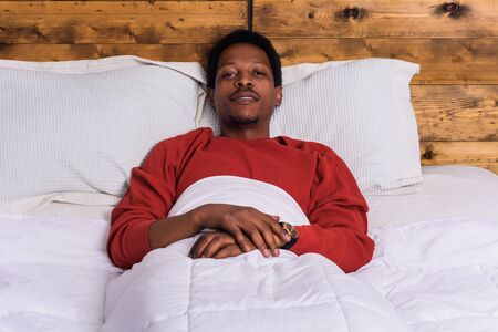 Portrait of young african man relaxing on bed at home.