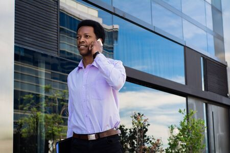 Portrait of young latin businessman talking on mobile phone in the city. Stock fotó