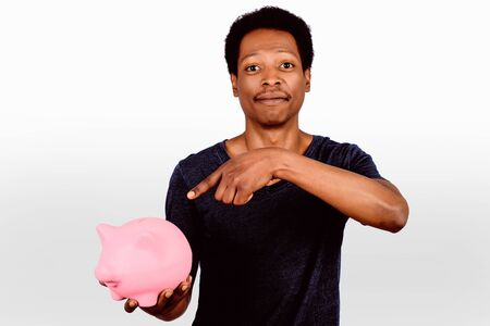 Portrait of black man putting a coin in a piggy bank on studio. Save money concept.