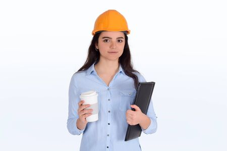 Portrait of female architect holding folders with a coffee on hand and helmet on head. Architect concept. Stock fotó